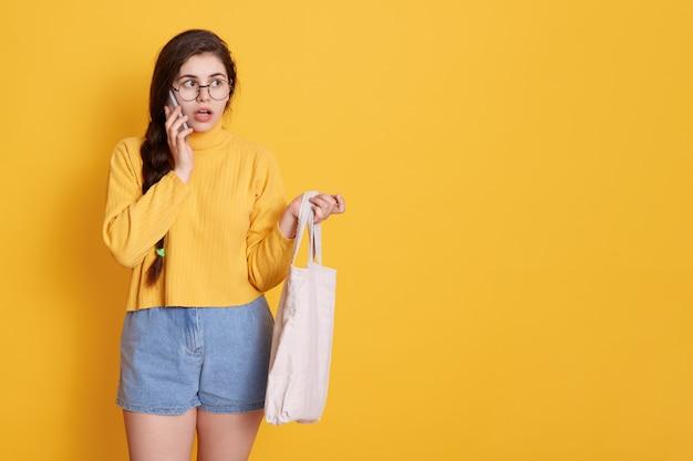 驚いた表情で誰かと話して、電話で黄色の壁に孤立したポーズをとって長い黒髪のショックを受けた若い女の子の肖像画。