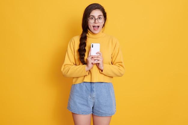 困惑した感情的な暗い髪の女性がスマートフォンを持ち、口を大きく開け、印象的な何かに驚かされ、黄色の壁に孤立したポーズをとって、プルオーバーとジーンズをはいて身に着けています。