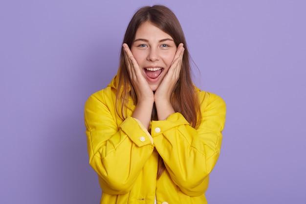 黄色のプルオーバーの魅力的な愛らしい女性の肖像画を間近し、明るいライラックの壁に分離された頬に手のひらを保ち、女性は幸せそうに見え、肯定的に表現します。