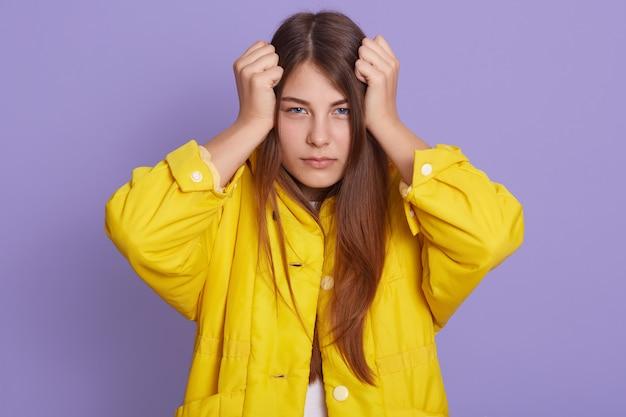 ライラックの壁にポーズをとって強い頭痛を持つ若いきれいな女性、黄色のシャツを着て、悲しそうな表情の長い髪を持つ女性。