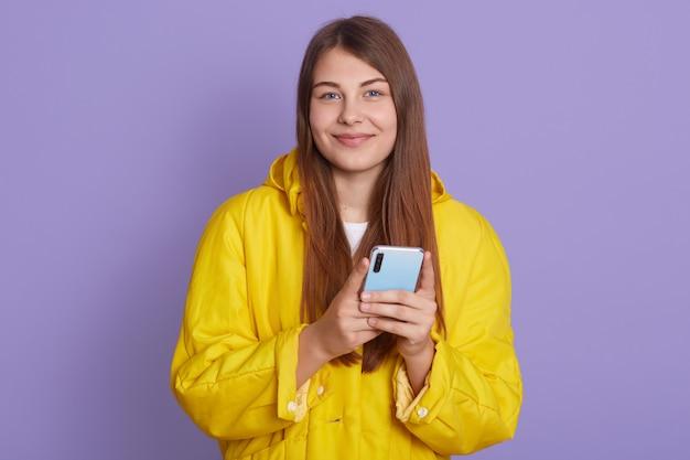 満足している素敵な女性は、現代の携帯電話を保持し、チャットで友人とオンラインでテキストをやり取りし、スタイリッシュな黄色のシャツを着て薄紫色の壁に立ちます。