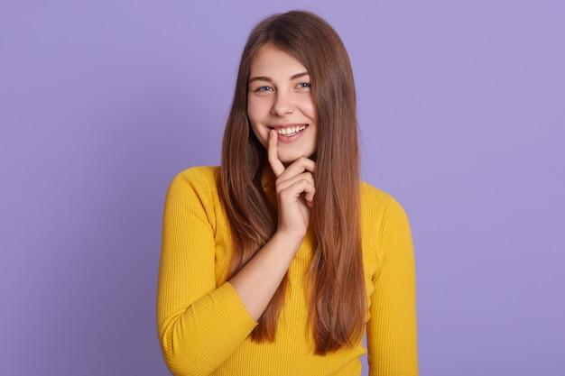 黄色のシャツを着て、ライラックの壁に立って、肯定的な感情を表現する唇の近くの指で幸せな笑顔の女性。