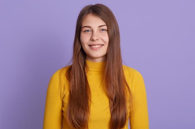 ライラックの壁に立って、黄色のカジュアルなセーターを着て、良い気分で魅力的な笑顔で若い幸せな女性の肖像画。