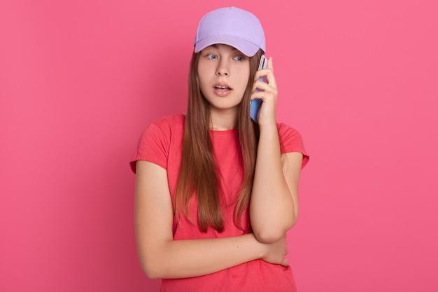 現代のスマートフォンを介して誰かと話しているカジュアルな服装を着て口を開けた女性。びっくりした表情で、バラの壁に孤立した大きな目で立っています。