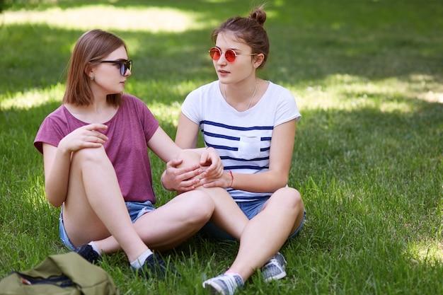 緑の芝生で組んだ足に座って、お互いに愛情を込めて見て、サングラスをかけている間、女性レズビアンは一緒に楽しみます