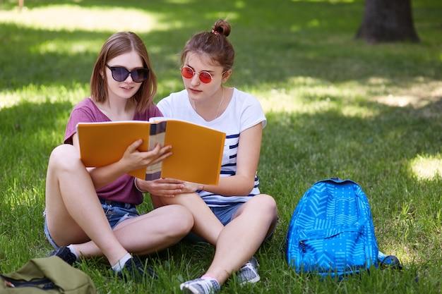 かなり女子学生がファッショナブルなサングラスをかけ、公園の緑の芝生に組んだ足を座って、本に焦点を当てています