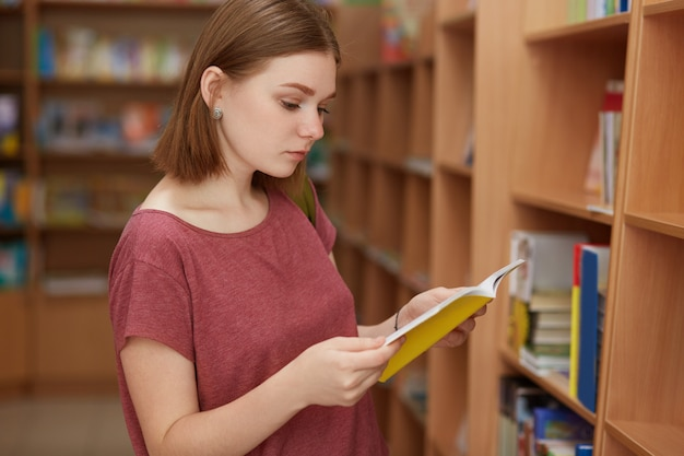 Внимательная читательница с короткой прической, стоит возле полок с книгами в библиотеке, читает рецензию, прежде чем выбрать, что читать