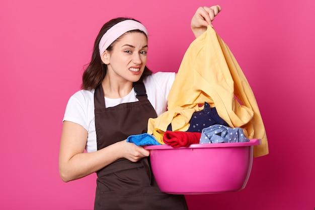 Отвращение брюнетка молодая домохозяйка держит таз полный грязного белья. горничная моет грязное белье. домохозяйка с белым обручем для волос