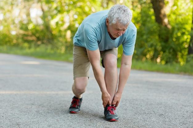 スポーティな健康な男性の年金受給者の屋外ビューは、アスファルトの上に立って、脚を伸ばし、筋肉を引っ張って、スポーツウェアやスニーカーに身を包んだ