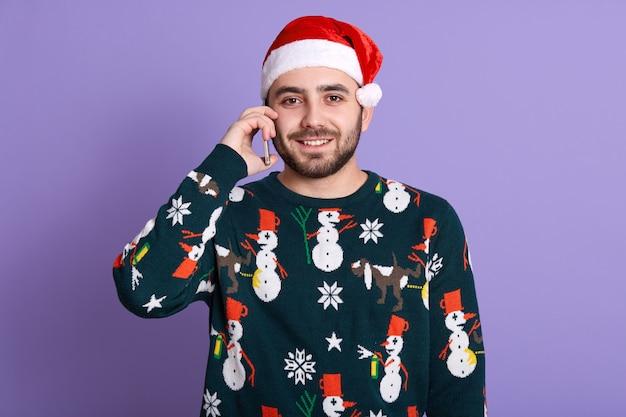 現代のスマートフォンを介して話している肯定的なクリスマスの男。携帯電話で話すサンタ帽子のひげを生やした男