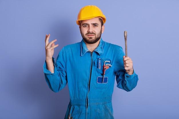 困惑した男性の配管工または自動車整備士は、どこに破損があるのか理解できず、肩をすくめて、困惑して手を上げます