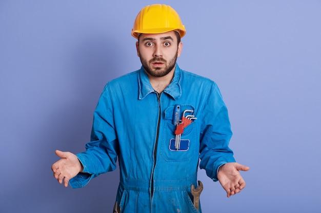 Удивленный потрясенный молодой строитель в желтом шлеме и синей форме, стоя с раскрытым ртом и раскинув руки