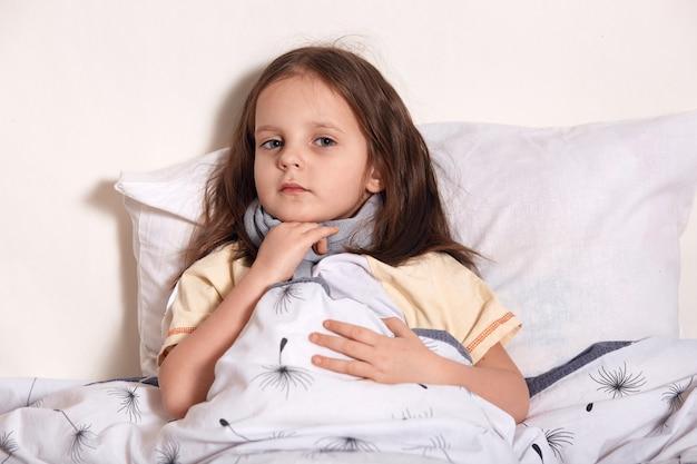 Горизонтальная картина расстроенного сладкого ребенка с теплым шарфом на шее, смотрящего прямо, касающегося шарфа, болящего в горле, больного