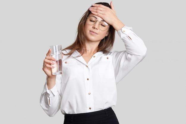疲れた過労の女性は、額に手をつないで、透明なメガネ、黒と白の服を着て、水のグラスを保持し、のどが渇いて疲労を感じ、白い背景に分離します。疲れ