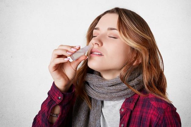 病気のきれいな女性が鼻を詰まらせ、点鼻薬を垂らし、鼻水に苦しんでいる