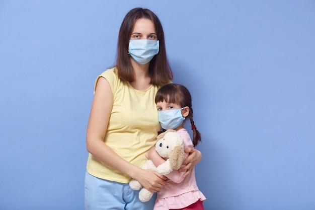 母と娘が医療用マスクを着用し、お互いをハグ