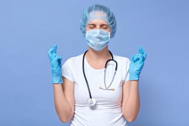 Портрет молодой женщины носит одноразовую шапочку, перчатки, медицинскую маску, позы со скрещенными пальцами
