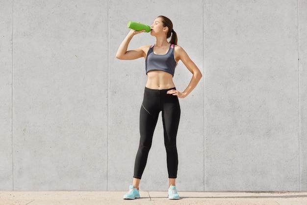 Спортивная женщина в спортивной питьевой воде из пластикового контейнера во время тренировки в гимназии держит руку на бедре