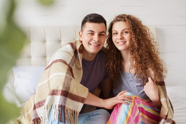 Веселая подруга и парень одеты небрежно, наслаждаются уютом под теплым пледом в спальне, имеют положительные эмоции