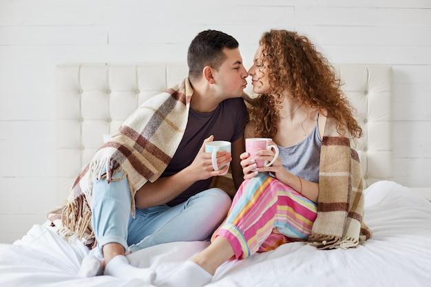 Счастливые женщины и мужчины имеют романтические отношения, пьют кофе или чай, покрытые пледом в спальне