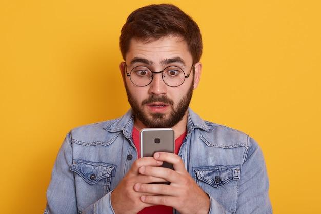 スタイリッシュな服でポーズをとって口を開けてショックを受けた表情で携帯電話を見て興奮している若いひげを生やした男のイメージ