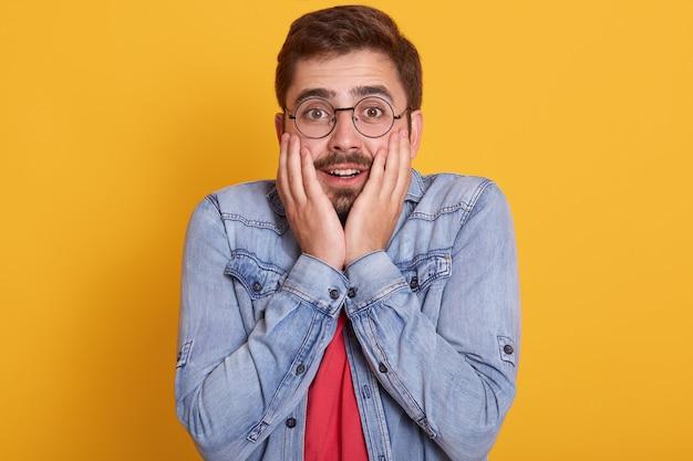 Удивленный молодой кавказец с очками и удивленным выражением лица, одетый в красную футболку и джинсовую куртку