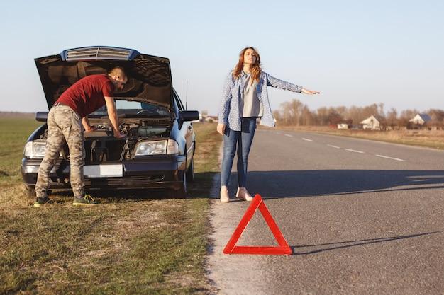 絶望的な女性は、助けが必要なときに道路上で車両を停止し、夫と一緒に車で移動し、エンジンで損傷を受けます