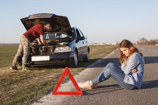 忙しい若い男性ドライバーが車の損傷エンジンの問題を解決しようとし、彼のガールフレンドが道路に座っている間、開いたフードの前に立っています。