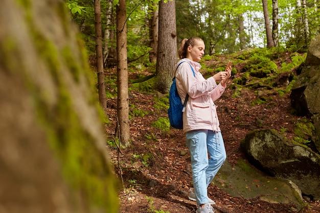 ピンクのジャケット、青いバックパック、ジーンズ、スニーカーを着て、スマートフォンを手に持ち、写真を撮り、接続を探し、休暇中にキャンプに行くヨーロッパの旅行者のプロフィール。ハイキングのコンセプト。