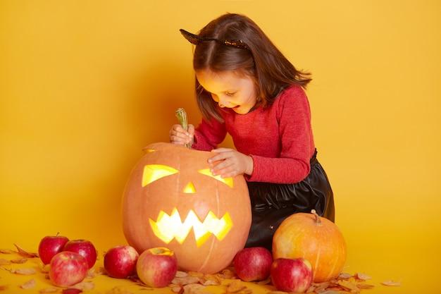 秋の黄色の葉、リンゴ、カボチャのハロウィーンの服を着た愛らしい面白い白人少女の肖像画