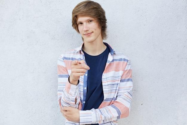 Ультрамодный мужчина при стильная стрижка нося вскользь рубашку указывая пальцем на камеру имея застенчивый взгляд изолированный над белой предпосылкой. подросток, выбирая что-то во время жестов пальцем