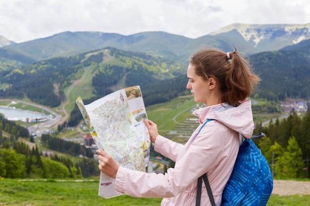 Профиль привлекательного молодого туриста теряется на ее пути, внимательно смотрит на карту, ищет правильный маршрут, стоит у холма