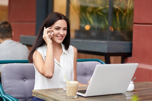 正装の肯定的な女性実業家、電話での会話、同僚との会話、ラップトップコンピューターを使用したビジネスレポート