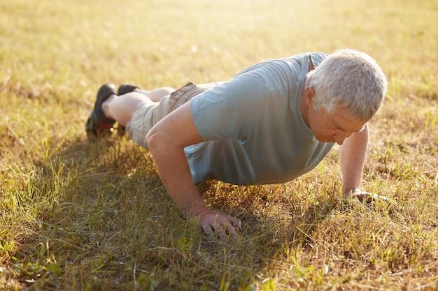 Спортивный пожилой активный мужчина делает отжимания на земле, одетый в спортивную одежду, нагревается в солнечный летний день, делает доску. здоровый образ жизни в любом возрасте. уход за телом и концепция спортивной мотивации.