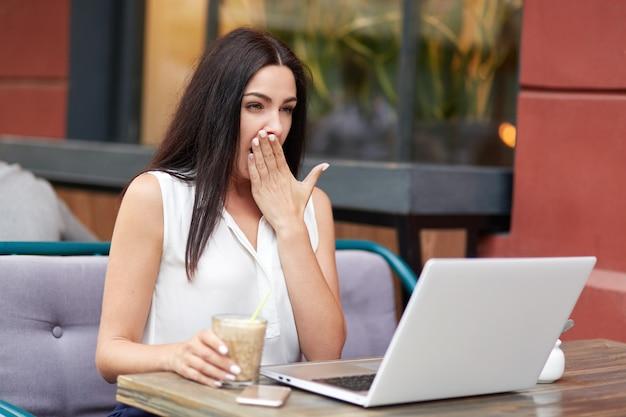 Усталая перегруженная молодая девушка-фрилансер зевает, как хочет спать, хочет отдохнуть, долго работает за ноутбуком, пьет коктейль