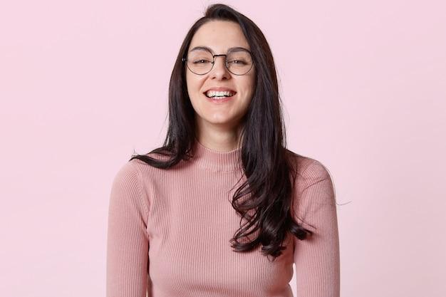 トレンディな素敵な眼鏡を持つ長い髪のブルネットの若い女性の笑い