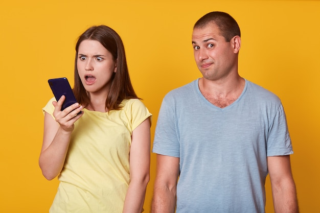 夫の電話を握り、口を開けてショックを受けた表情で彼のメッセージを確認する驚いた女性の画像
