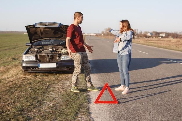 カップルは道路上で主張し、壊れた車に問題を抱え、パニックに陥っており、何をすべきかわからない。赤い警告三角形が他のドライバーに損傷について警告する。夫と妻は自動車の近くの関係を整理する