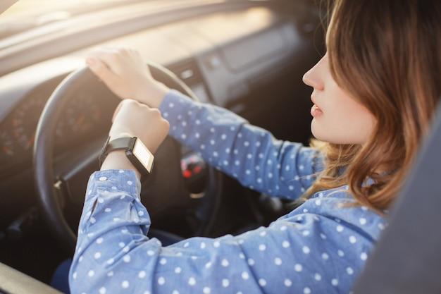 Занятая молодая женщина водит машину и смотрит на часы, застрявшие в пробке