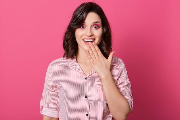 Внутренняя съемка удивленной женщины покрывая ее рот руками пока представляющ над розовой стеной и с раскрытым ртом, женщина нося вскользь обмундирование. концепция эмоции людей.