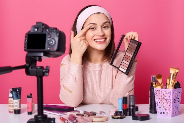 魅力的な若い女性は、インターネット経由でお金を稼ぎ、三脚に固定されたカメラの前に座って、アイシャドウを適用し、明るい表情を持ち、美容製品に囲まれ、成功したブロガーである