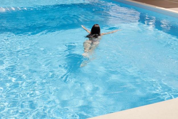 Темноволосая женщина с купальником плавает в бассейне с голубой водой в роскошном спа-салоне или в отеле, проводит свободное время, наслаждаясь летними каникулами в бассейне. праздник, расслабиться, отдыхая концепции.