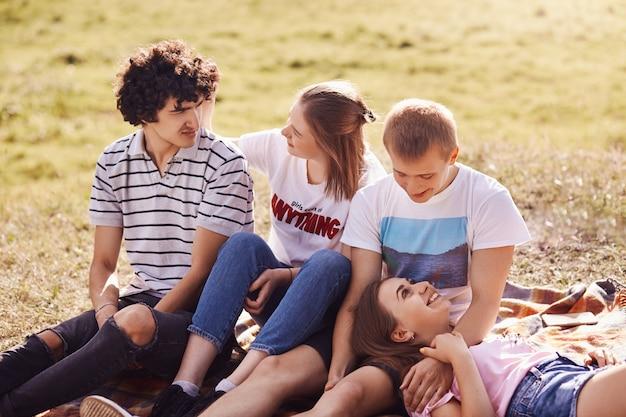 Четверо веселых друзей имеют радостные выражения, проводят свободное время на зеленом поле, общаются друг с другом, отмечают успешно сданные экзамены, одеты в повседневную летнюю одежду, имеют привлекательную внешность
