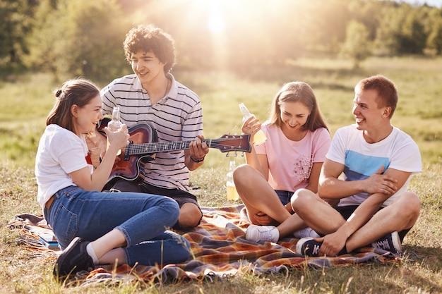 フレンドリーな若者の水平ショットは楽しいし、週末に自由な時間を一緒に過ごし、地面に座って、ギターに歌を歌い、おいしい飲み物を飲み、晴れた日を楽しんでいます。友情と人々の概念。
