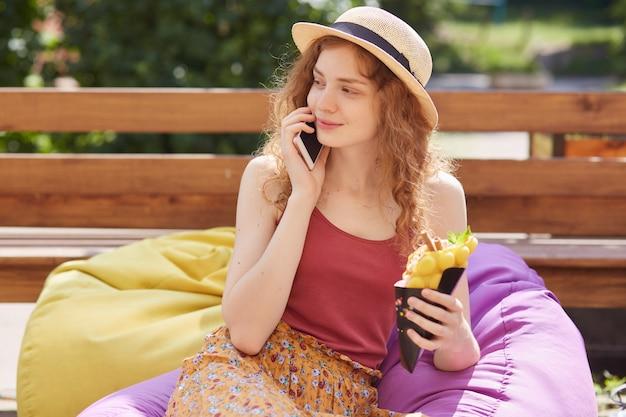 お手玉でポーズ、電話で話している、会話をしている、よそ見、デザートを持っている、赤いトップ、麦わら帽子とカラフルなスカートを着て、気分が良い、喜んでいるほっそりしたモデルの画像。