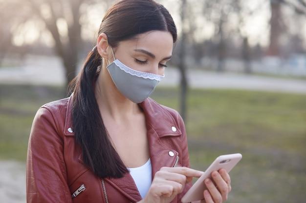 ポニーテールの暗い髪の女性のイメージ、庭に立って、携帯電話を手で押し、番号を呼び出す、集中して見える