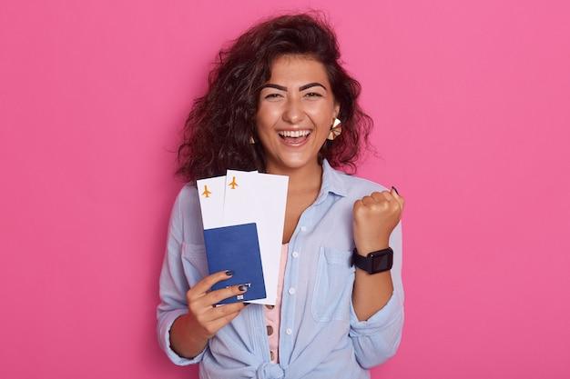 Фото обрадованной студентки с паспортом и посадочными талонами в руках