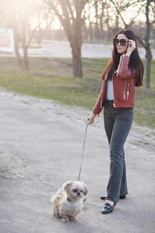 Молодая женщина выгуливает свою белую мальтийскую собаку на поводке в солнечный день, надевает брюки, кожаную куртку и солнцезащитные очки, оставаясь одна на улице