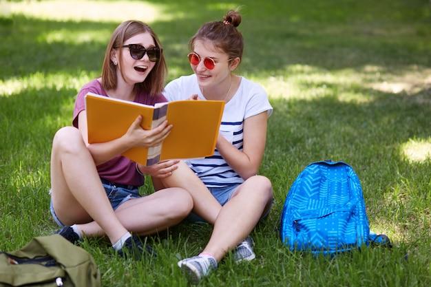 緑の芝生で組んだ足に座り、春の天候を楽しみ、前向きな表情を持ち、授業の後休憩している間、幸せな女性学生の水平ショットはリラックスした気分です。人、残り、レジャーのコンセプト