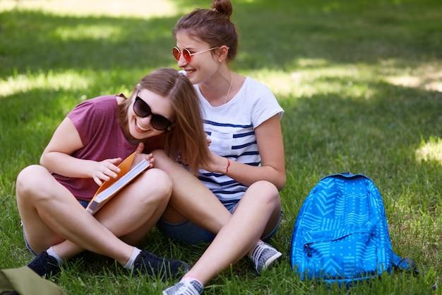 面白い女性の仲間は一緒に楽しみ、漫画の逸話や面白い話をしたり、大学での授業の後に休憩したり、緑の芝生で屋外の家の準備をしたり、本を開いたりします。人と幸福